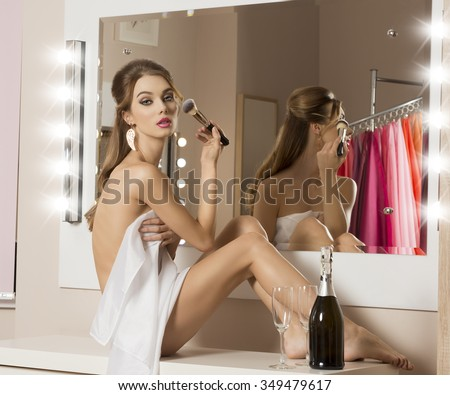 stunning woman doing make-up in changing room, sitting in changing room and covering her nude body with white towel. A bottle of champagne and glass near her for new year toast. Preparing for party