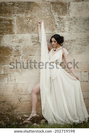 Stunning woman in white long dress, holding its folds and showing her beautiful leg.