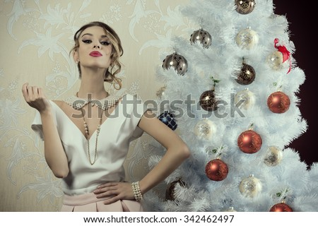 stunning woman with aristocratic fashion style and pose near decorated christmas tree with elegant clothes, precious pearl necklace and stylish make-up
