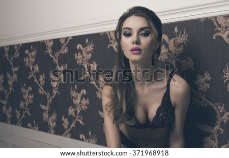 stunning woman with long brown hair and cute make-up posing with elegant lace lingerie and looking in camera with charming expression