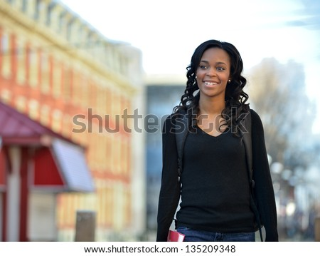 Stunning young African American female student walking with backpack and boot - outside on campus - stock photo