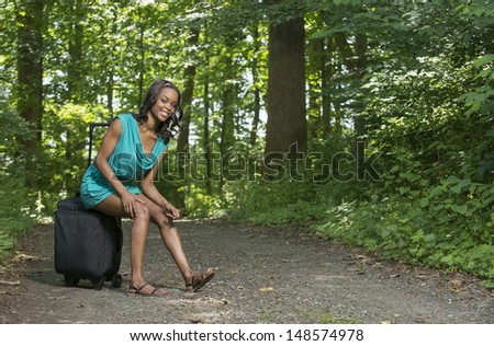 Stunning young African-American woman in a blue dress standing along a country road with a black suitcase - smiling at viewer
