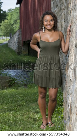 Stunning young biracial woman in green sundress standing next to covered bridge and stone wall foundation - rural