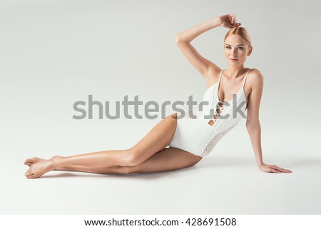 Stunning young blonde beauty posing in a white swimsuit. People on a diet. Perfect body.  - stock photo