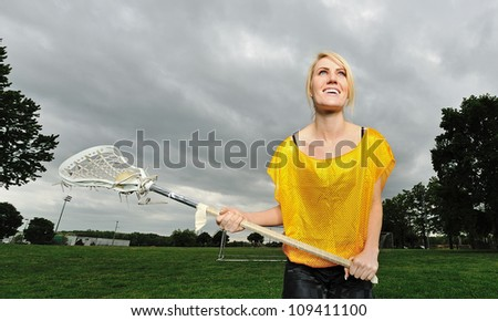 Stunning young blonde female lacrosse player - in yellow practice jersey and holding stick - stock photo