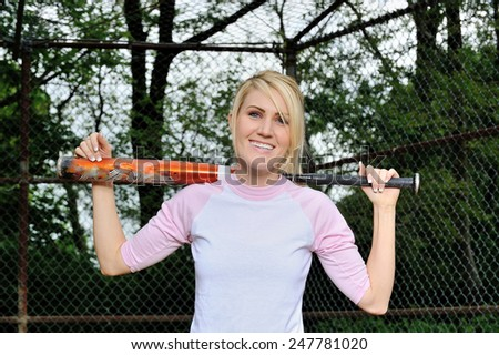 Stunning young blonde female softball player in pink and white baseball jersey shirt - holding bat over shoulders - stock photo