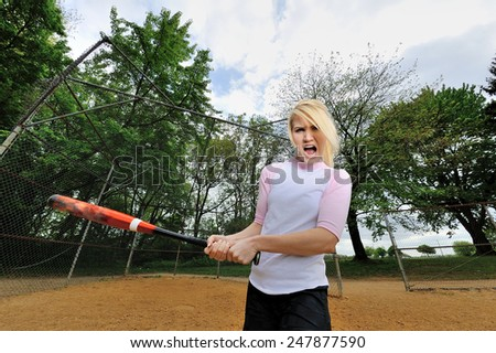 Stunning young blonde female softball player in pink and white baseball jersey shirt - holding bat and swinging - shot with fisheye lens - stock photo