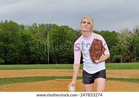 Stunning young blonde female softball player in pink and white baseball jersey shirt - pitching - stock photo