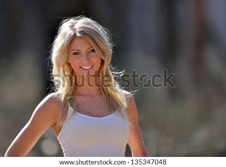 Stunning young blonde model in a white tank top and afternoon sun - country or rural portrait - copy space to right of frame - stock photo