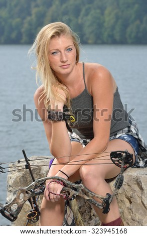 Stunning young blonde woman archer sits in front of lake holding her compound bow - flannel shirt tied off around her waist - stock photo