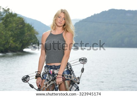 Stunning young blonde woman archer stands in front of lake holding her compound bow - stock photo