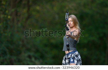 Stunning young blonde woman archer stands ready to fire an arrow from her compound bow - flannel shirt tied off around her waist - stock photo