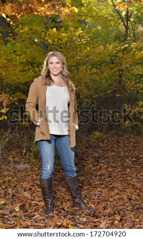 Stunning young blonde woman in beige colored sweater, jacket and blue jeans standing outside in autumn - sun highlighting her hair - fall