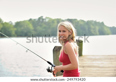 Stunning young blonde woman in denim shorts and tank top sitting on pier and fishing - stock photo