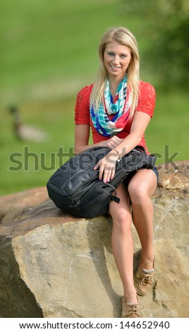 Stunning young blonde woman leaning sitting on top of a large rock with her backpack on a college campus - student or education stock - stock photo