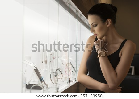 Stunning young brunette , watching jewel inside a jewellery , she stand near the shop window indoor .