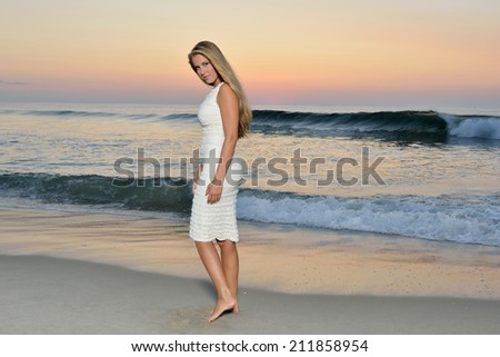 Stunning young Caucasian woman in white dress stands in the surf on beach at sunrise - sun is rising behind model
