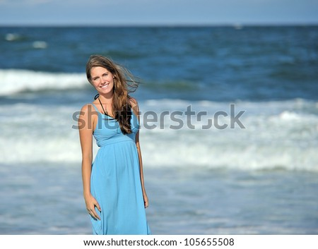 Stunning young Caucasian woman standing in front of the ocean surf in a blue sun dress