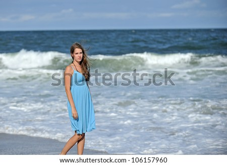 Stunning young Caucasian woman standing on a beach in a blue sun dress - looking at viewer as waves roll in behind her
