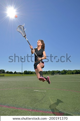 Stunning young female lacrosse player shooting as she leaps in the air, sunshine directly overhead - motion - stock photo