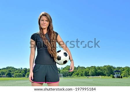Stunning young female soccer (futbol) player standing on field (pitch) holding ball against side - stock photo