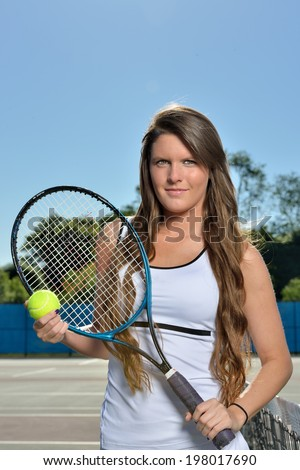 Stunning young female tennis player holding racket and ball at net under a blue sky and bright sunshine