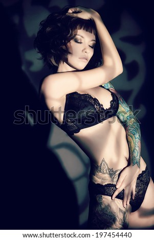 Stunning young woman  alluring in sexual lingerie over dark background. - stock photo