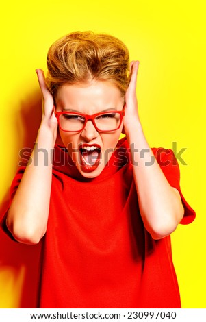 Stunning young woman in red dress and elegant spectacles shouting at camera. Stress, depression. Fashion.