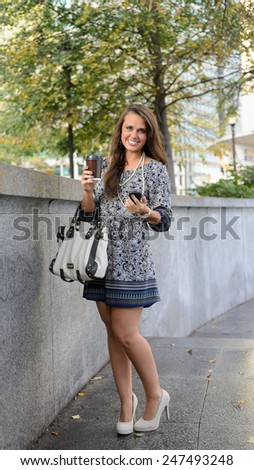 Stunning young woman standing in city park wearing blue print dress holding smart phone, coffee cup, and purse - stock photo