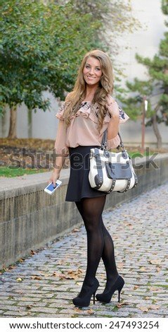 Stunning young woman standing on cobble stone sidewalk holding purse and cell phone - business  - stock photo