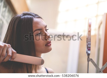 Stunning young woman straightening her hair with an iron - Beautiful woman with makeup getting ready in the bathroom