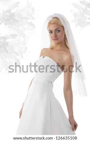 stunning young woman with smooth hair in marriage day wearing white dress and veil. Some flower on background - stock photo