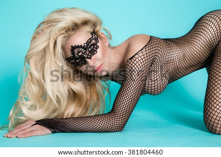stunningly beautiful sexy catwoman woman with long blond hair and slim figure in carnival mask in a provocative pose sensual and seductive looks at the camera wearing a black translucent bodystocking - stock photo