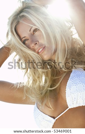 Stunningly beautiful young blond woman in backlit by sunshine and wearing a white bikini