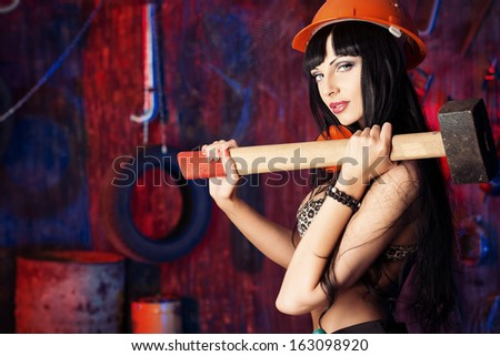 Stunningly sexual girl posing with tools in the old garage.  - stock photo