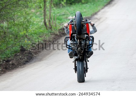 Stunt rider is riding on the one wheel of his motorbike - stock photo