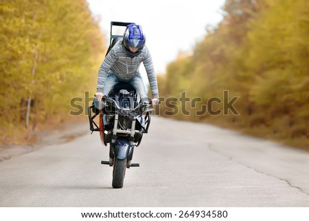 Stunt rider making stoppie on the autumn forest background - stock photo