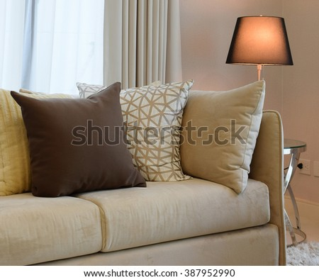 Sturdy brown tweed sofa with grey patterned pillows and lamp