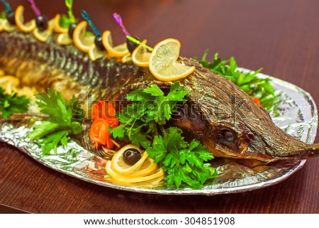 sturgeon baked with greens fruits and vegetables - stock photo
