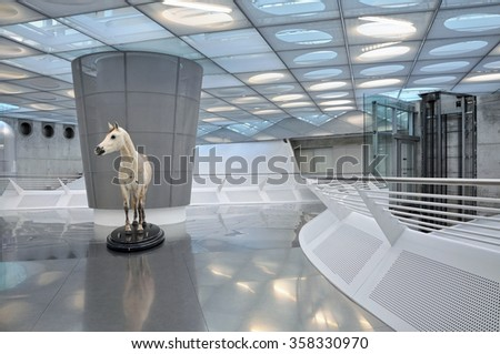 STUTTGART, GERMANY - APRIL 22TH, 2014: Interior of the modern museum of cars Mercedes-Benz. Fragment of the exposition with standing white horse. Stuttgart, Germany on April 22, 2014. - stock photo