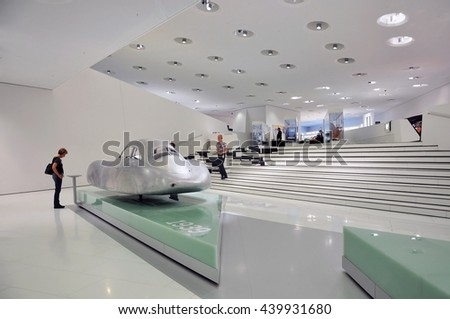 STUTTGART, GERMANY - APRIL 21, 2015. The white interior of the Porsche cars museum. The exposition futuristic cars with visitors. Stuttgart, Germany on April 21, 2015. - stock photo