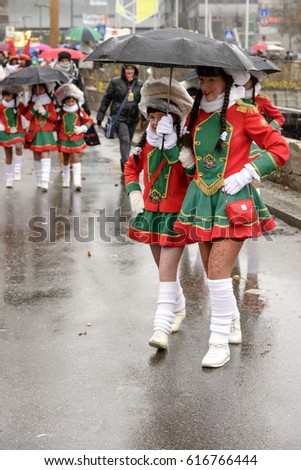 STUTTGART, GERMANY - FEBRUARY 28:  majorettes smile while marching under black umbrellas . Shot under rain at  Carnival parade in city center on feb 28, 2017 Stuttgart, Germany