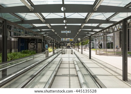 Stuttgart, Germany - June 25, 2016: Car parking area with moving walkway and people in the distance at the airport terminal in Stuttgart, Germany. - stock photo