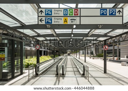 Stuttgart, Germany - June 25, 2016: Car parking area with signs providing directions to the various carparks, moving walkway and people in the distance at the airport terminal in Stuttgart, Germany. - stock photo