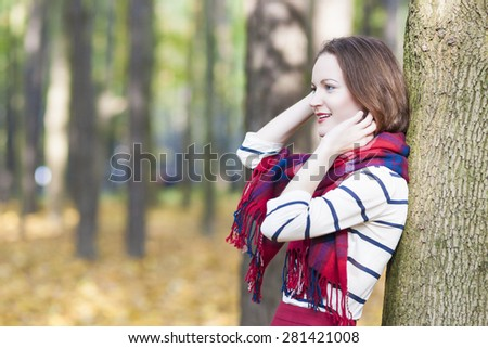Style and Fashion Concept: Caucasian Female Model Dressed in Stylish Clothing. Standing Outdoors in Forest. Horizontal Image Orientation - stock photo