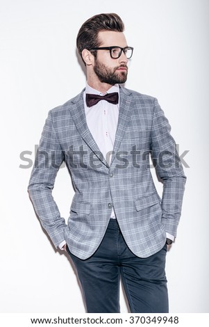 Style and intelligence. Handsome young man wearing suit and glasses keeping hands in pockets and looking away while standing against white background - stock photo