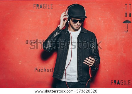 Style and music. Handsome young man adjusting his headphones and looking at his smart phone while standing against red background - stock photo