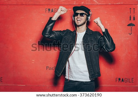 Style and music is his passion. Handsome young man in headphones gesturing and keeping mouth open while standing against red background - stock photo