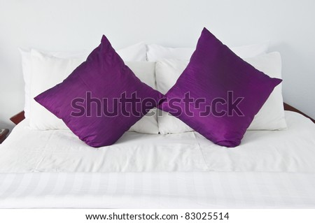style bedroom interior with double purple pillows on white wall - stock photo