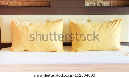 style bedroom interior with double yellow pillows. - stock photo